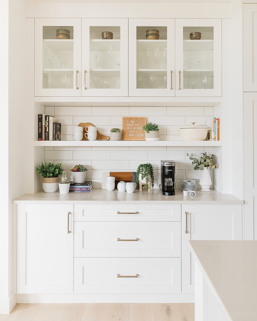 White kitchen cabinets with glass uppers and open shelves in the middle and plants, dishes and cookbooks displayed.