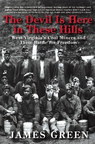 about a dozen young men, both Black and white, in early 20th century mining gear pose for a group photo