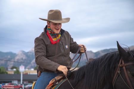 Boy having a blast horseback riding on Colorado family vacation!ng fun!