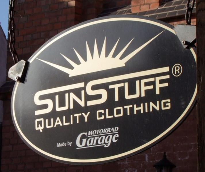 SunStuff Wachsbekleidung Logo vor Motorrad Garage