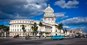 blue skies and classic cars in front of Havana's government building, Cuba