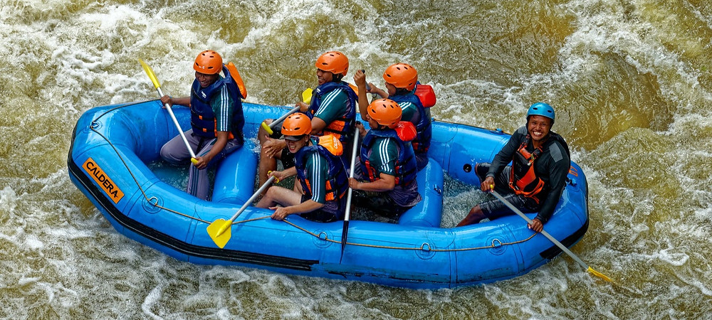 Group of people rafting in a blue raft