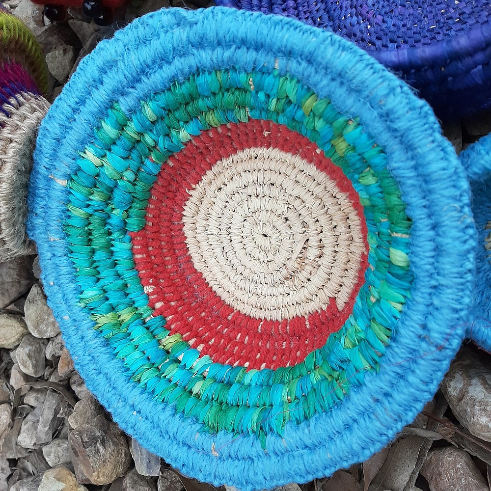 This is an image of a aqua and blue basket. Towards the centre there is a red ring and then a beige centre circle.