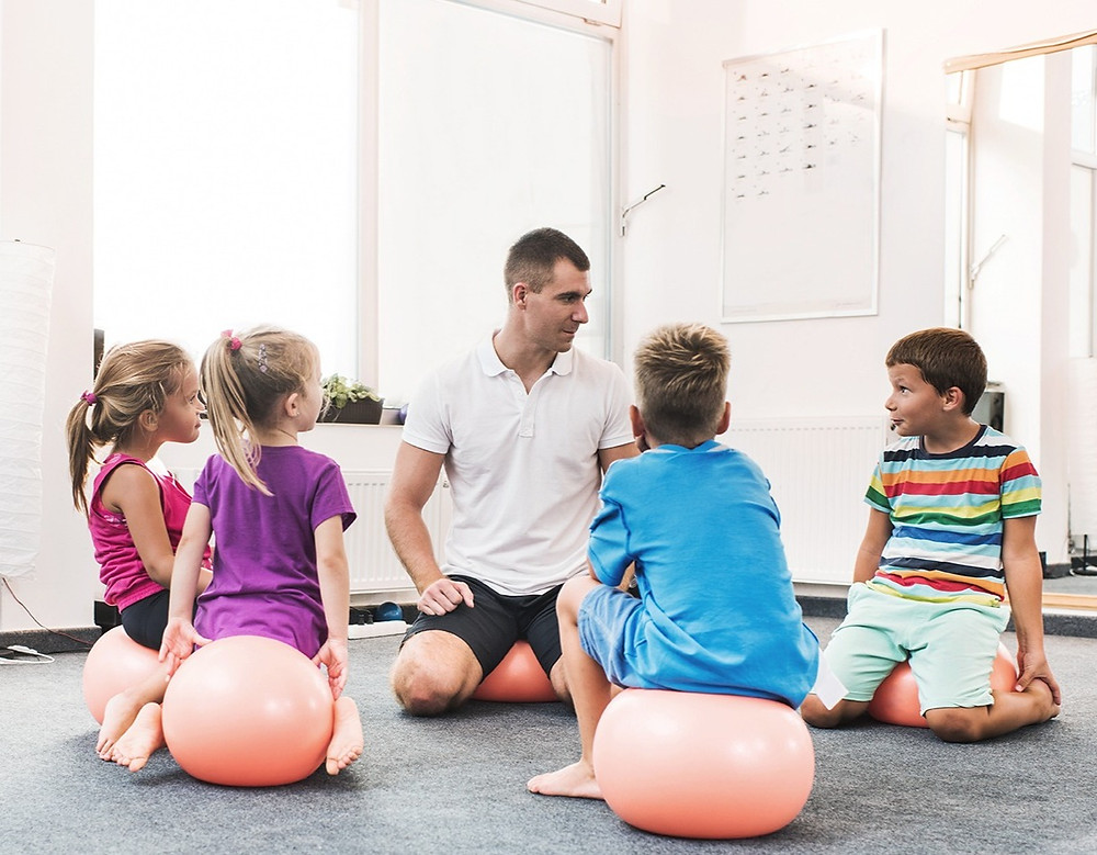Group of 4 students and a teacher sit on exercise balls on the floor.