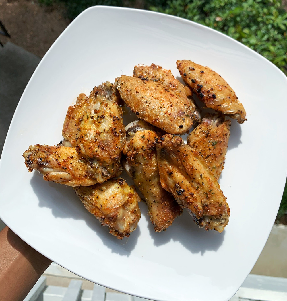 crispy baked chicken wings stacked on a white plate; overhead shot