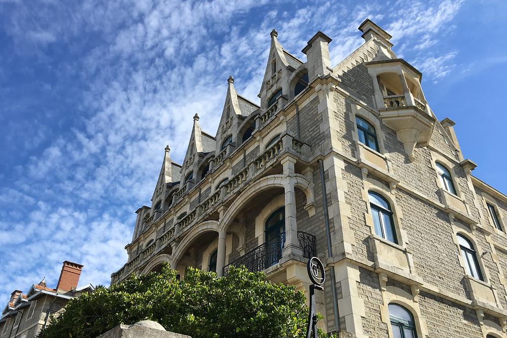 """La Villa Cyrano """"ex-Labat"""" de Biarritz. Vista de su elegante e imponente fachada de estilo neogotico con toques modernistas sobre cielo azul y nubes blancas."""
