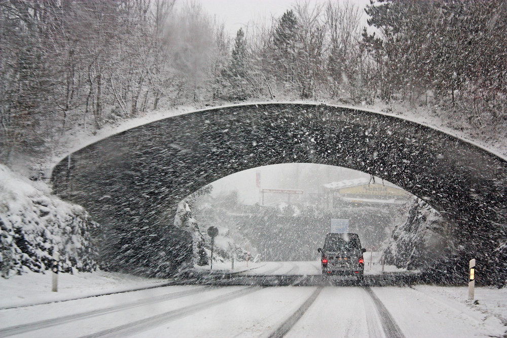 Truck drives under a bridge during a blizzard