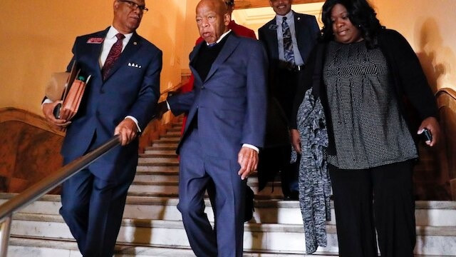 John Lewis descending down stairs with members of his team.