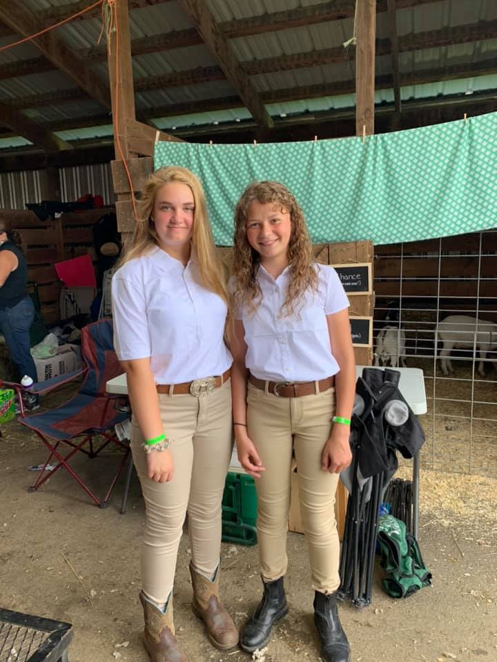 older 4-h student helping a younger 4-h student at the farm fair