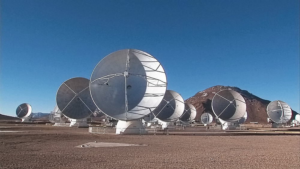 An image of the ALMA telescope array, with 9 or more large radio antennae pointed towards the camera atop a dry, arid mountain.