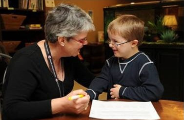 A picture of a nurse talking to a young boy with Down syndrome