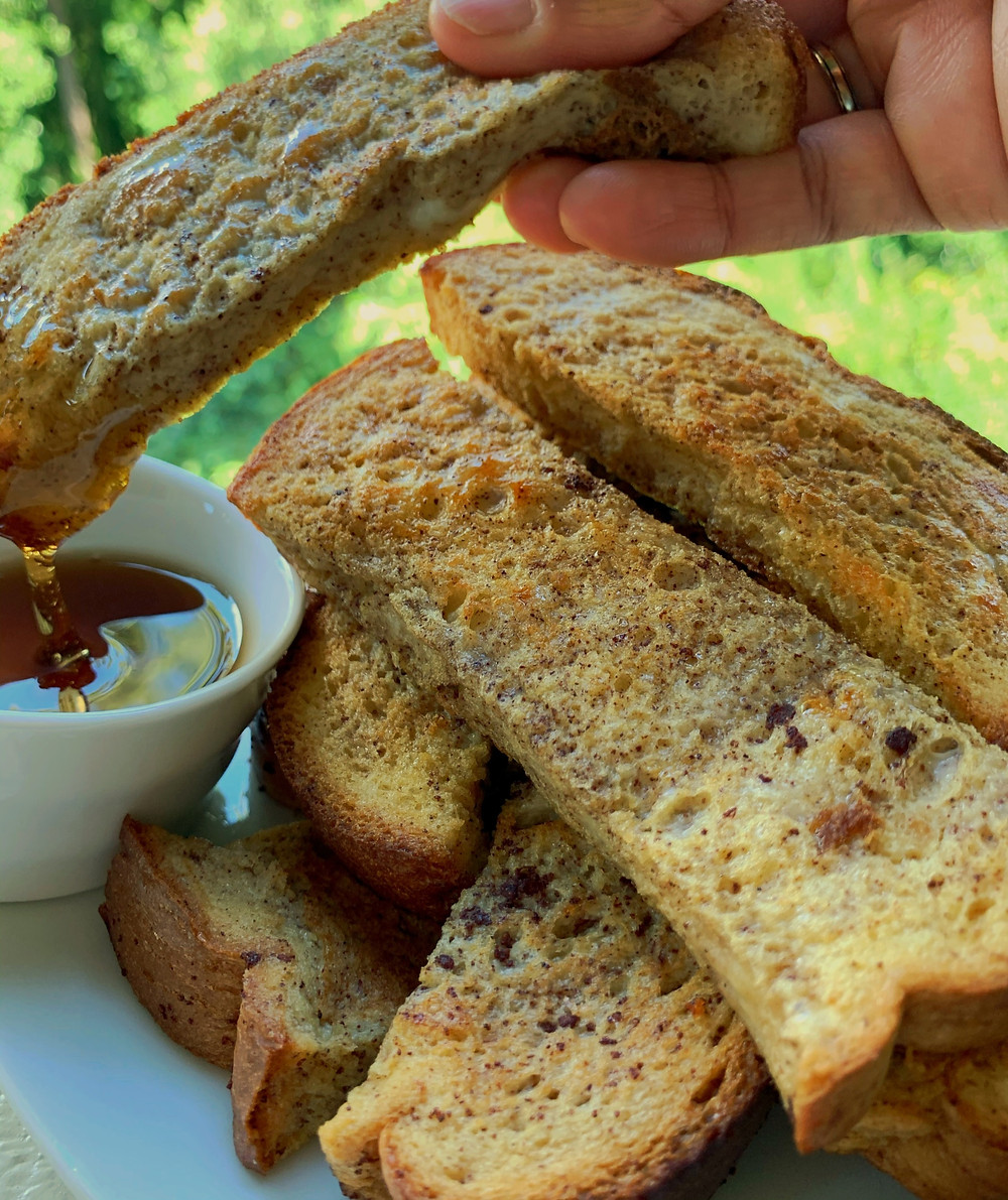a hand dips a french toast stick in maple syrup; more french toast sticks are stacked below