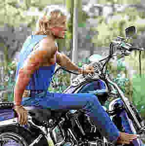 Johnny jeune et pieds nus sur une Harley Davidson bleue