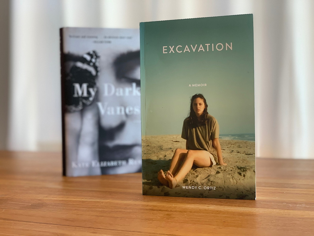 A copy of Excavation in close shot with My Dark Vanessa behind it. On a table.
