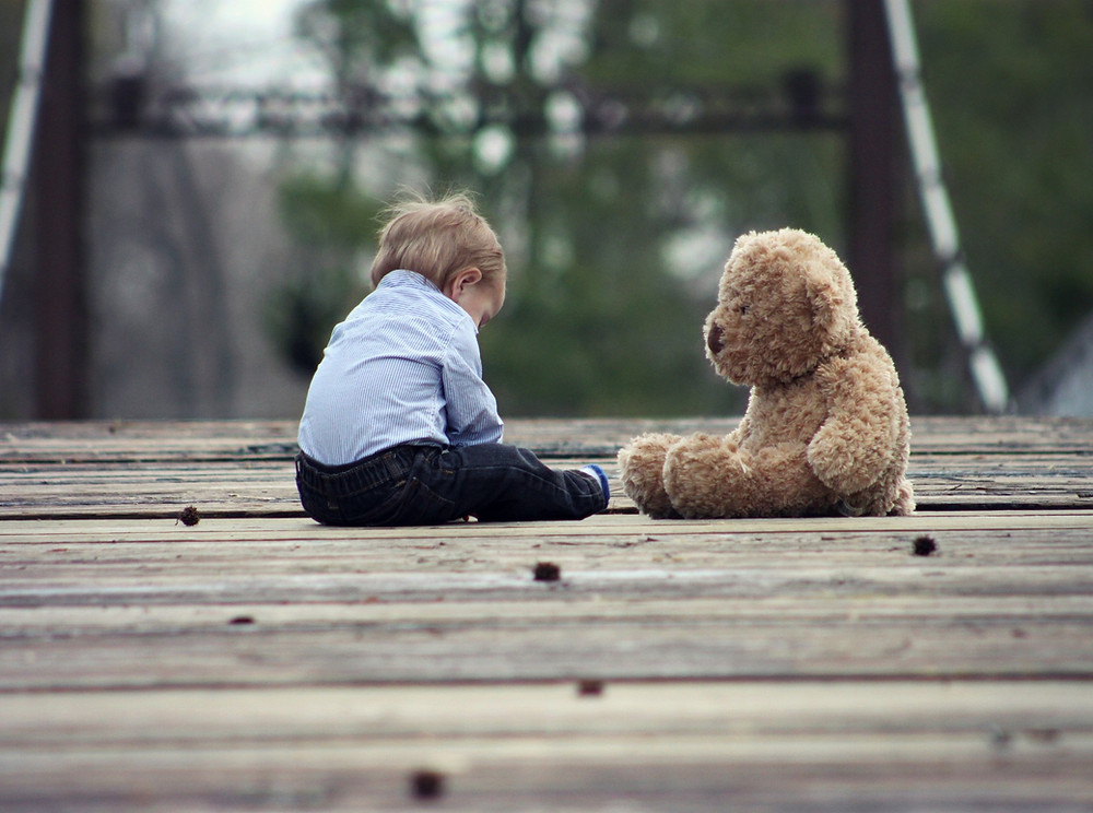 A toddler and a large teddy bear are sitting on a wooden platform near a wooded area.