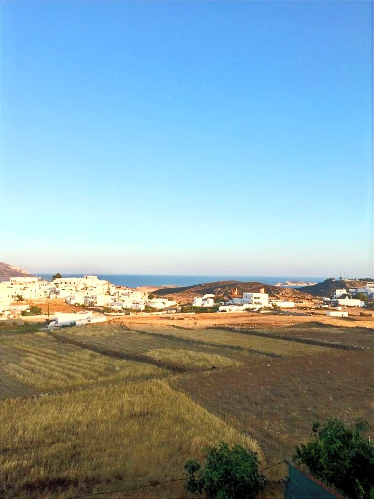 Landscape of Kimolos island, blue sky horizon and white washed buildings