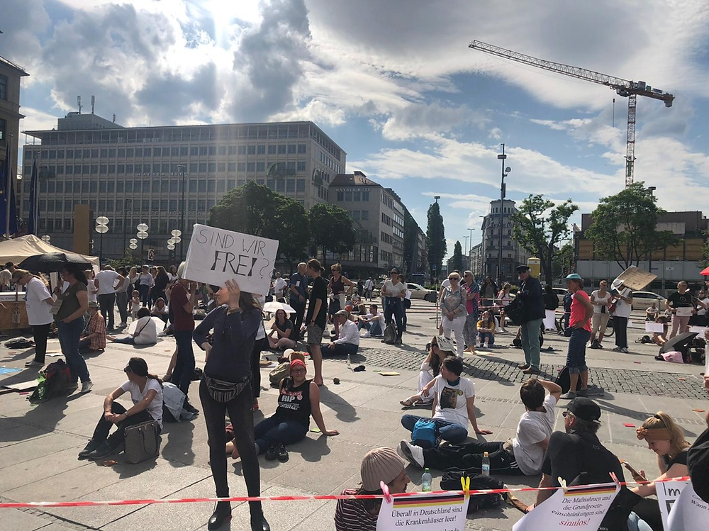 "Figure 5: Protestors holding a sit-down protest in Munich's Karlsplatz. The signs read: ""Are we free?"", ""Everywhere in Germany hospitals are empty"", ""The restrictions of fundamental rights are unjustified""."