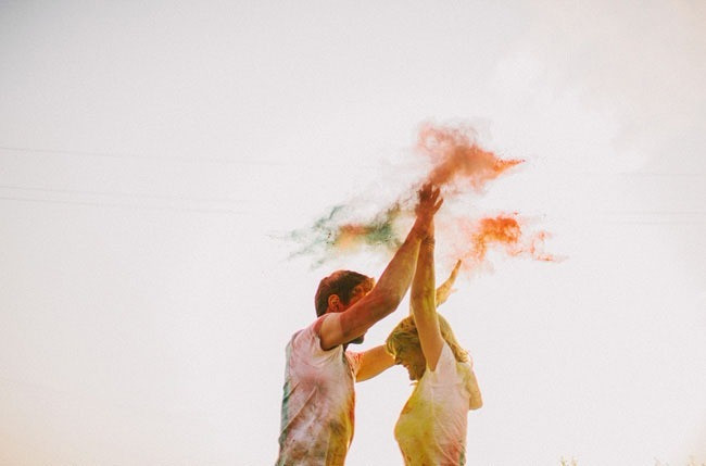 Wedding Photoshoot Props: Couple holding hands in air with burst of colored powder