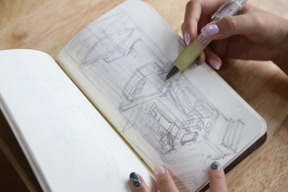 họa sĩ hoạt hình tại DeeDee Animation Studio đang vẽ phác thảo ra sổ vẽ
