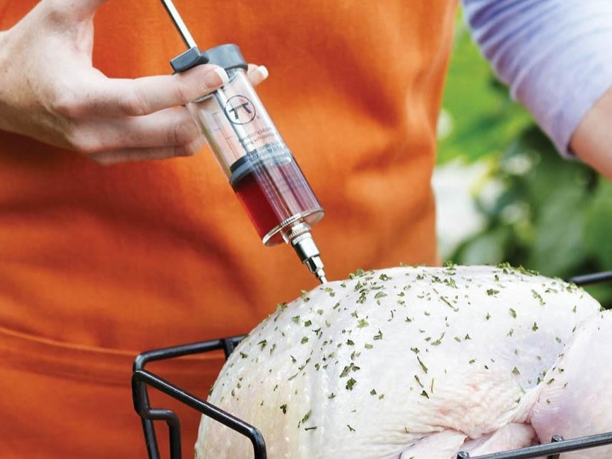 woman wearing an orange apron injecting a turkey with brine