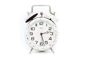 Slightly rusted white metal alarm clock showing nearly 2:30