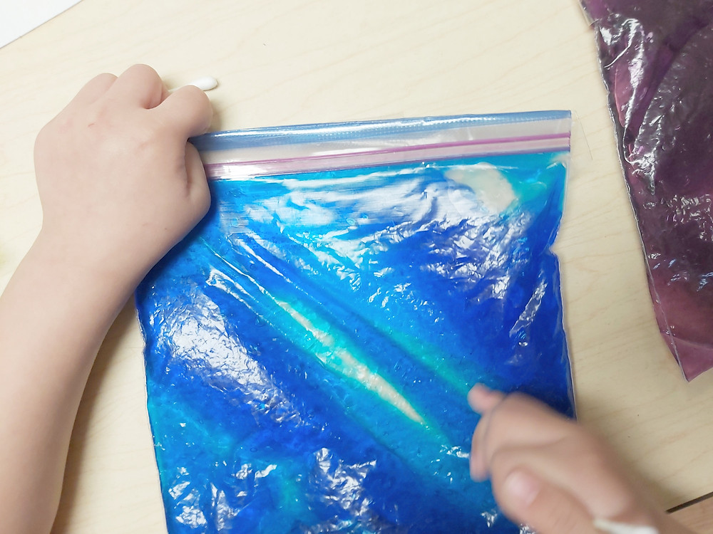 preschooler using sensory writing bag to write letters