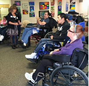 Four students in wheelchairs are sitting in a semi-circle, watching a female instructor in a black shirt and grey skirt give instructions