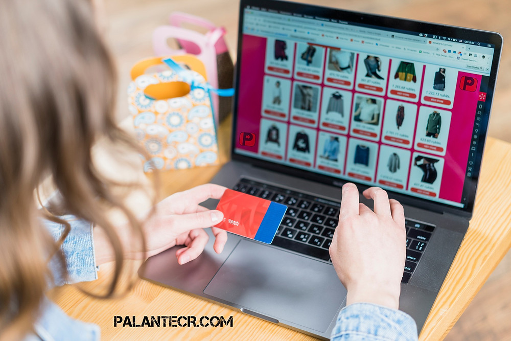 En la imagen se ve una compradora online con su computadora portátil y su tarjeta de credito con el texto: [PalanteCR.com}