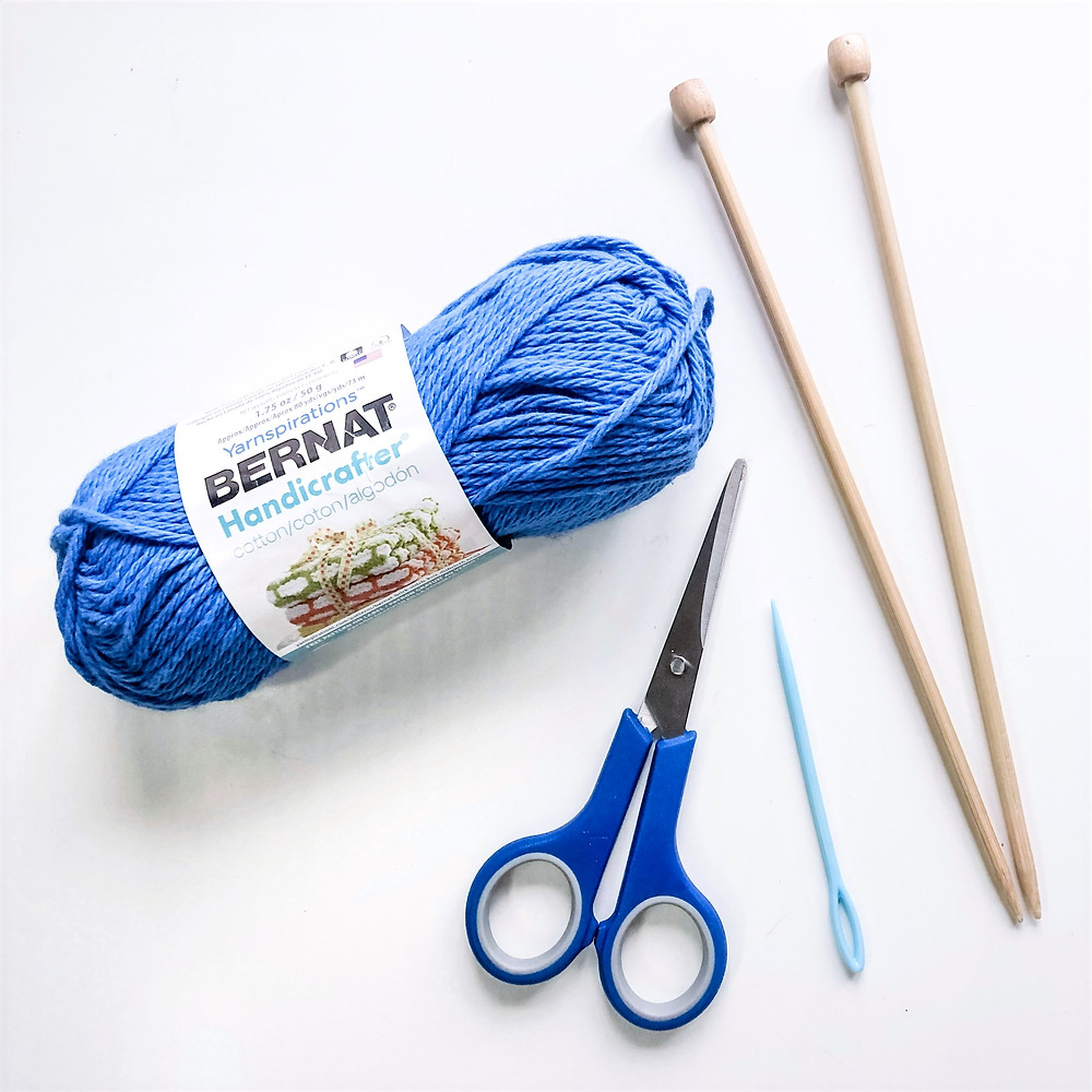 A ball of blue cotton yarn, a pair of knitting needles, a pair of scissors and a tapestry needle on a white background.