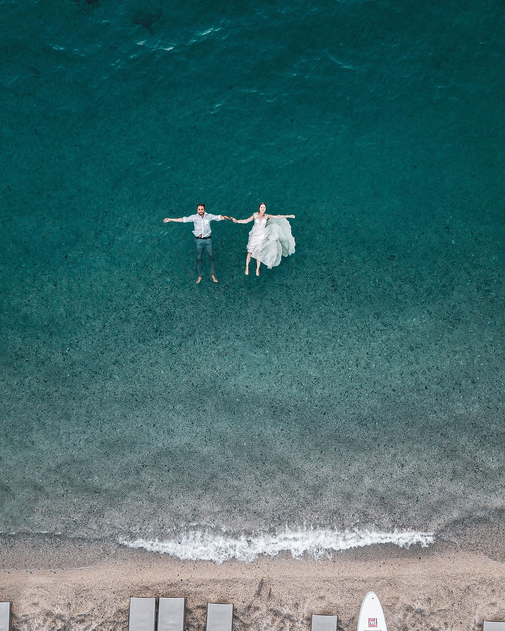 Man and woman floating on blue beach wedding picture.