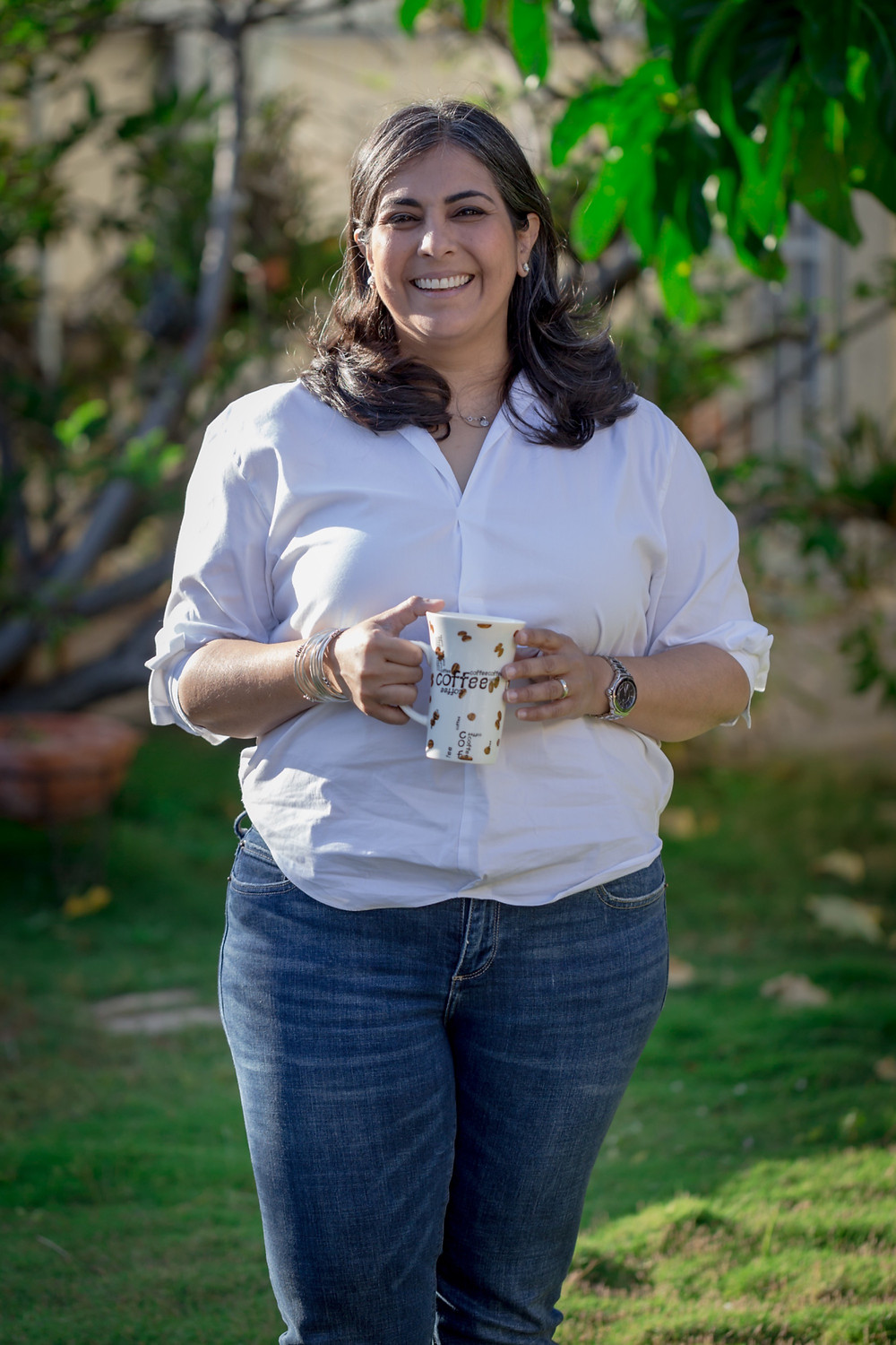 Kirti , the consultant, holding tea in a garden.