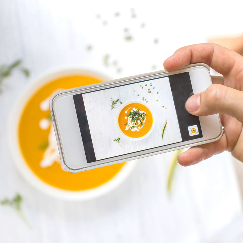 Birds-eye view of a cell phone being held up while taking a photo of a bowl of yellow soup.