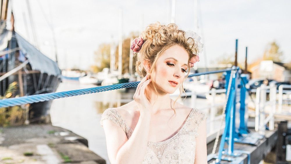 Bride with up do and flowers in her hair. Autumnal bridal make up. Bride poses for Essex wedding photographer Laura Jane Photography.