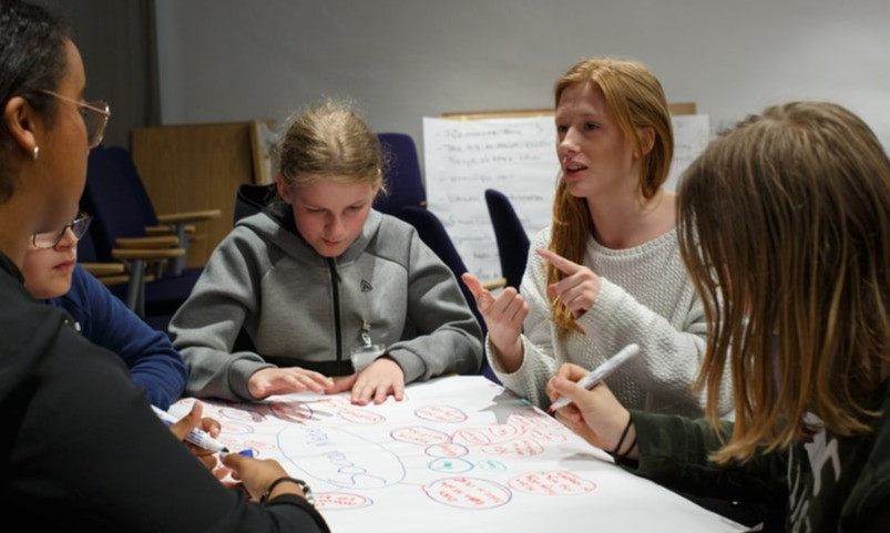 Group of teenage girls studying BTEC vocation qualification writing on flipchart paper