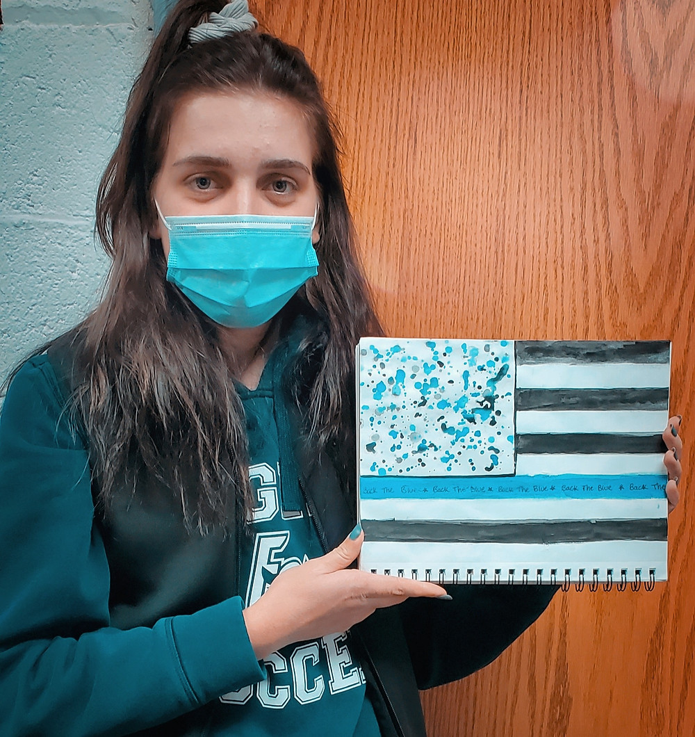 "High school junior, Gabriella Angelucci holding ""Back the Blue"" Artwork Eastern Christian"