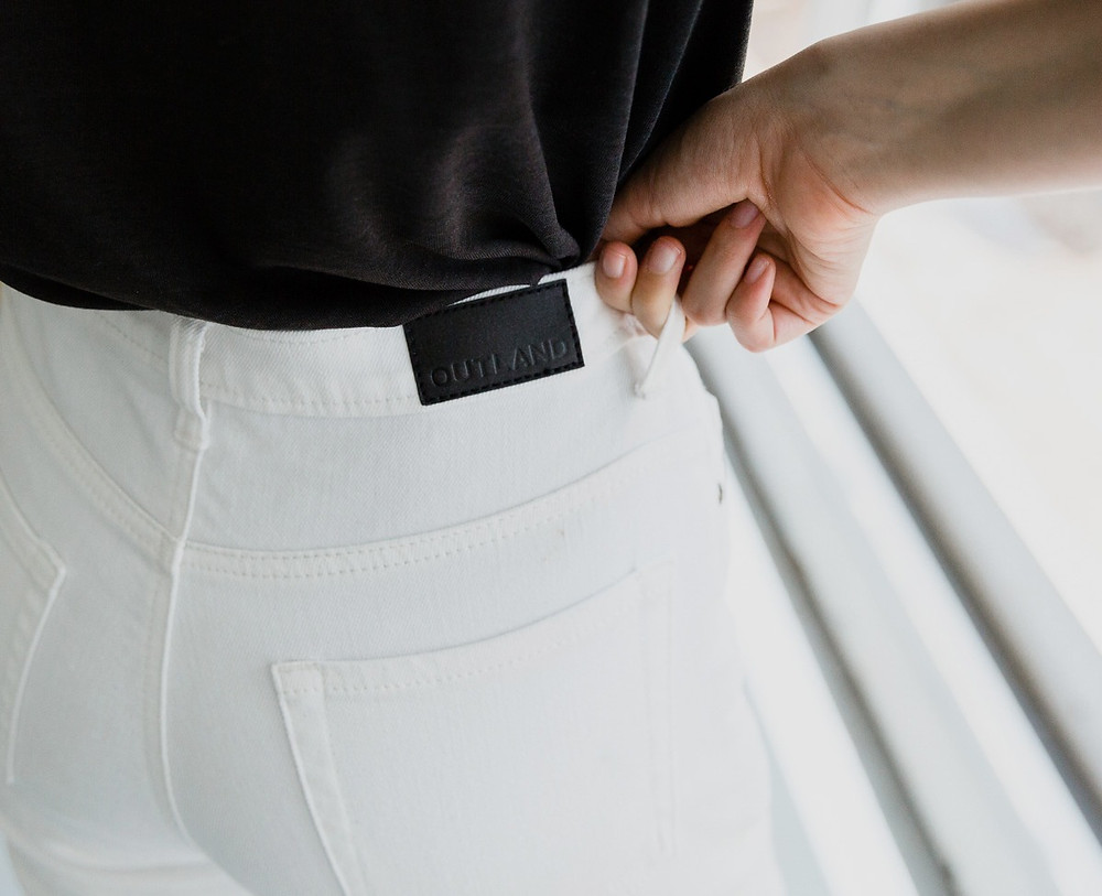 A hand pulls up a pair of white Outland Denim jeans by the belt loop.
