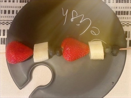 Picture of strawberries, bananas and blueberries on a wooden skewer.