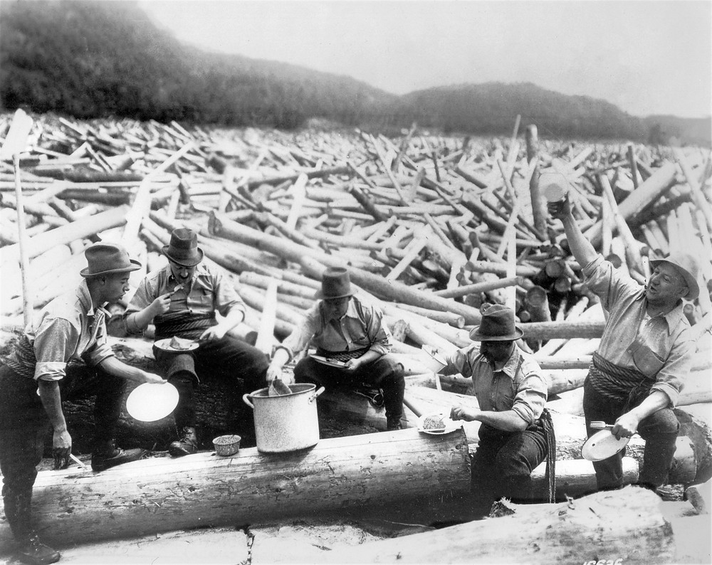 Loggers enjoying lunch on a log jam in the Gatineau River between Cantley and Chelsea, 1910. Photo Courtesy Gatineau Valley Historical Society