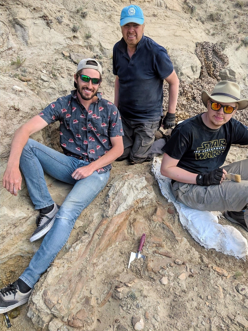 Intern Aaron and two participants pose next to the left femur of a duckbilled dinosaur.