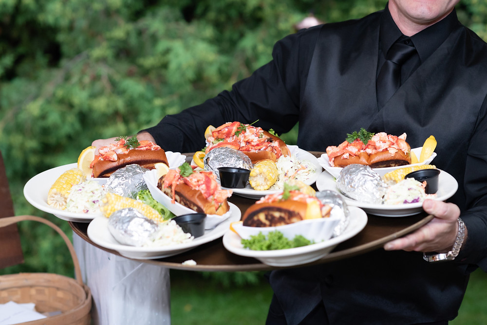 waiter holding a plate of lobster rolls