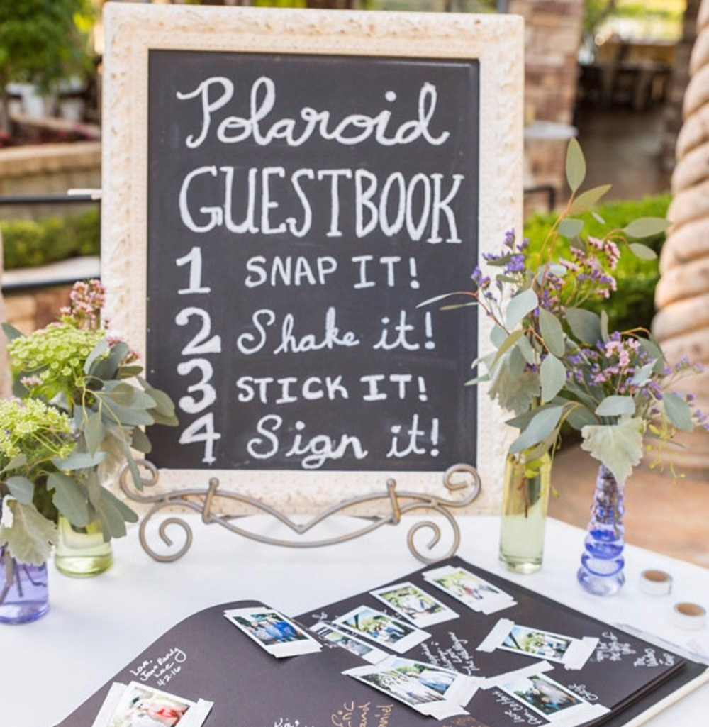 A Polaroid wedding selfie station with guest photos stuck in a book