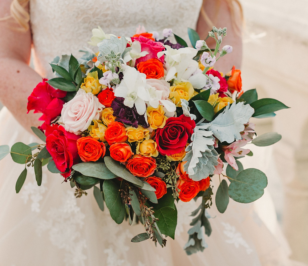 A bride holds her beautiful, brightly colored bridal bouquet
