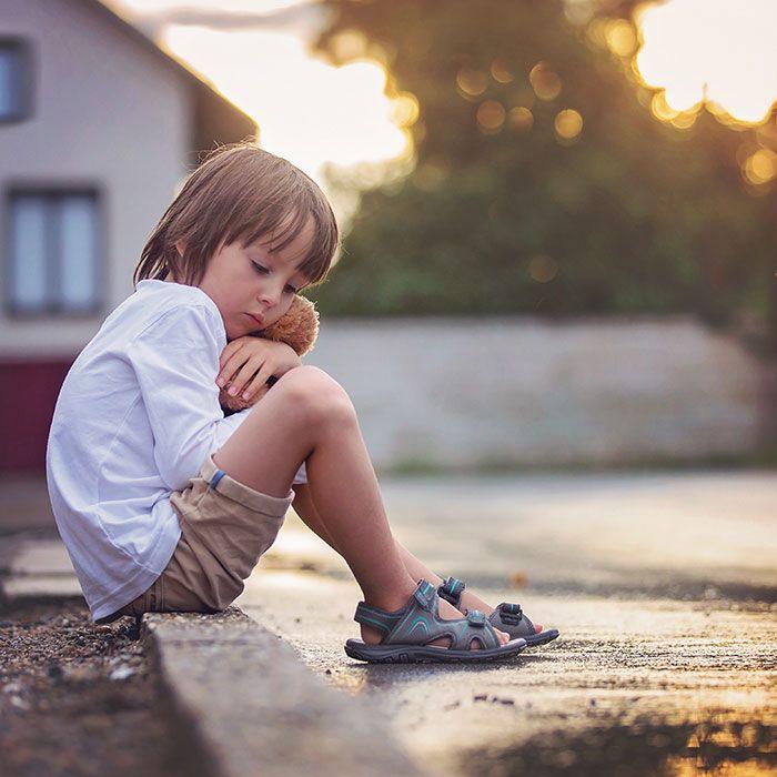 Тажно дете седи на тротоар во близина на домот и ја гушка својата плишана играчка