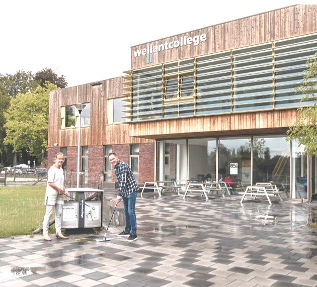 Karin Hille en Eddie Bakker ruimen zwerfvuil op bij het Wellantcollege in Naarden.