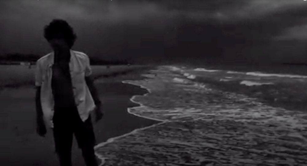 Dim black and white image of man walking towards us on a beach, waves crashing in close to his feet.