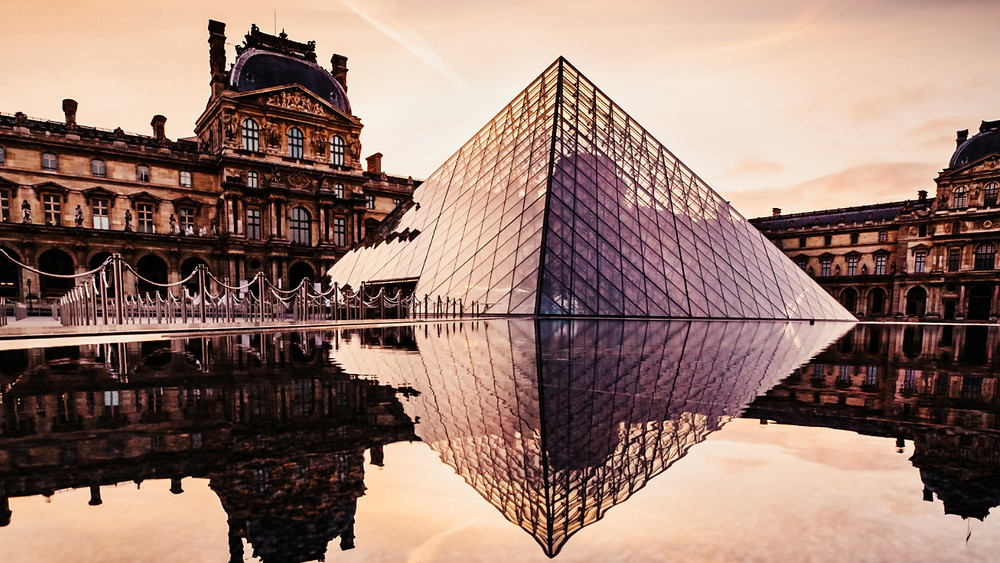 A shot of the Louvre Pyramid featuring great lighting and architecture