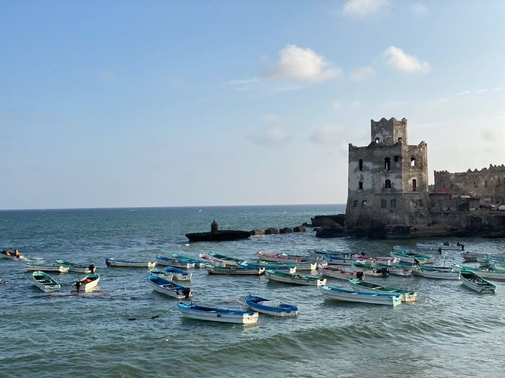 The Mogadishu Lighthouse is the most iconic landmark building in the city, simultaneously representing its glorious past, disastrous years of civil war, and the ruinous present. The lighthouse was built in early 1900s by Italians on a pier next to the harbor on the right and the most luxurious waterfront on the left. Hotels, banks, and large villas lined up the waterfront next to the lighthouse making Mogadishu the true jewel of Africa. Fast forward to today – and everything is in ruins. The abandoned lighthouse stands as a bizarre monument to a nuclear-like apocalypse that has brought Mogadishu down to essentially rubble. Local fishermen live inside and work on their fiberglass boat hulls nearby. All the once grand somali-Italian style architecture around the lighthouse now consists of bullet-ridden skeletons and utter destruction. But, despite all this, life goes on – and kids splash in the water, fishermen take boats out to see, and the area is even safe to get out of the car and walk around (with my four Kalashnikov-armed bodyguards forming a solid perimeter around me).