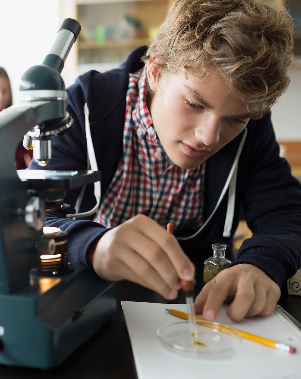 teenage boy in science lab completing school experiment GCSEs