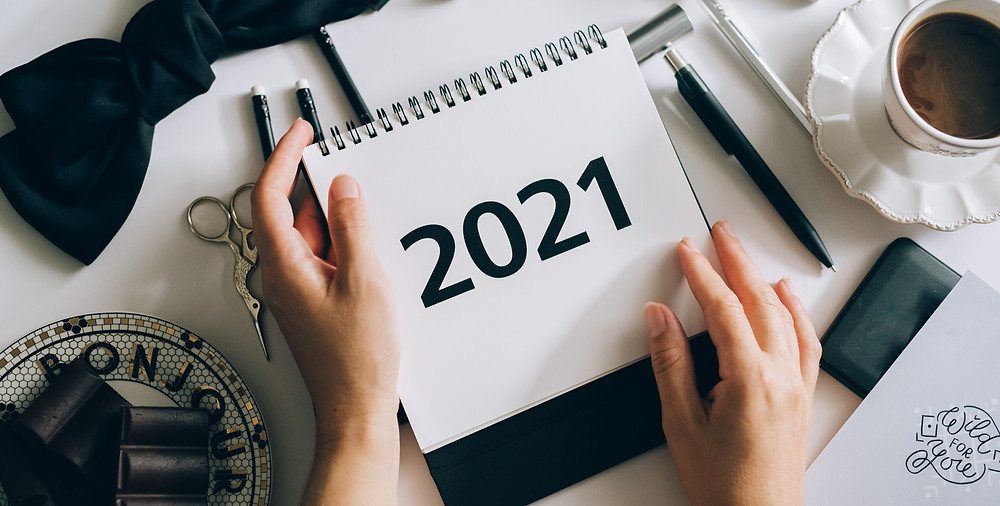 [Image Description] A woman opens a calendar for 2021 at her dining table