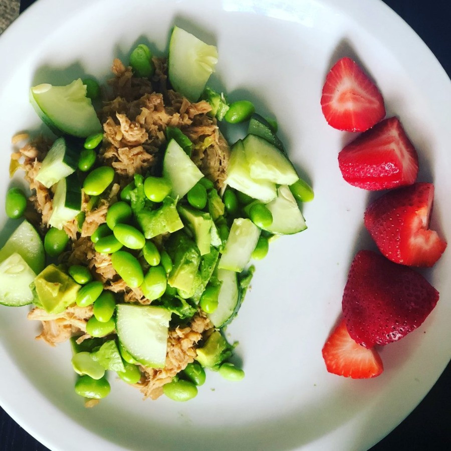 chicken with edamame and cucumbers mixed together with strawberries on the side